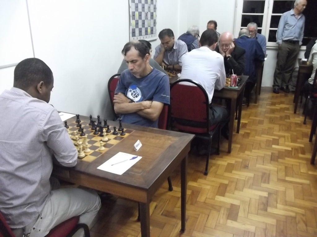 ALEX com carga máxima! Dez enxadristas jogando nas cinco mesas à esquerda! Ao fundo, Paschoal Mendes visitando o torneio