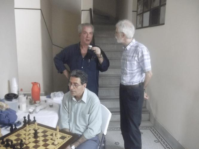 Sérgio Sundaus, assíduo visitante dos torneios da ALEX, conversa com o Mestre Nacional David Borensztajn, que toma seu cafezinho enquanto Antonio Elias pensa na posição de sua partida.