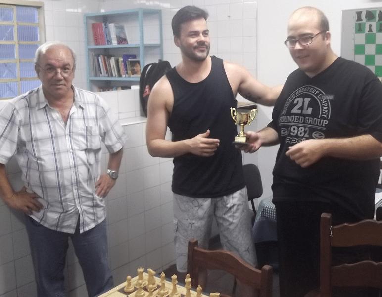 Rodrigo Zacarias, do Clube Municipal, entre o árbitro Selmo Bastos, à esquerda, e Werner Nunes, à direita, foi o Campeão do Torneio de Rápidas