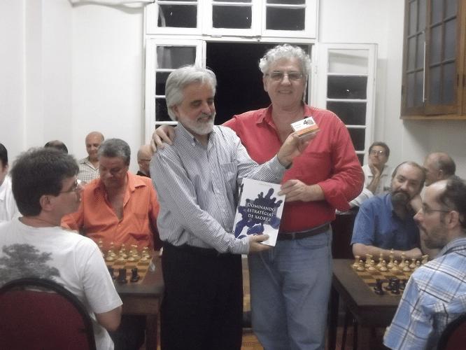 O mais novo sócio da ALEX, Luiz Alberto da Luz, entrega a Álvaro Frota o livro prêmio e o mini troféu diploma de Campeão Geral do Memorial Dijalma Caiafa