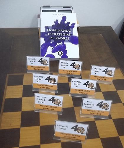 """O Livro Prêmio """"Dominando Estratégias de Xadrez"""" de Johan Hellsten e os Mini Troféus Diploma de Menção Honrosa, Campeão Sênior 80+, Campeão Sênior 60+, Campeão Classe """"C"""", Campeão Classe """"B"""", Terceiro Colocado Geral, Vice Campeão Geral e Campeão Geral."""