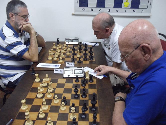 Luiz Sérgio Tiomno enfrenta Carlos Alves Rolim enquanto Irahy Ribeiro de Carvalho, após ter dado seu lance, pensa mais uma pouco na posição.