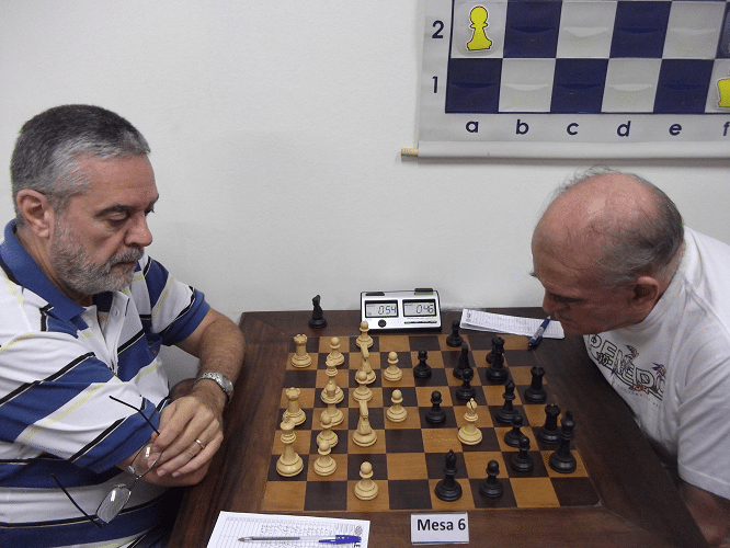 Luiz Sérgio Tiomno aguarda a retomada de seu bispo enquanto Carlos Alves Rolim reflete se seria melhor retomar de peão ou de bispo.
