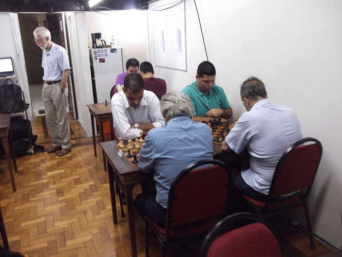 Visão das mesas à esquerda de quem entra no clube. Próximo à porta está Sérgiu Sundaus, visitando o torneio.