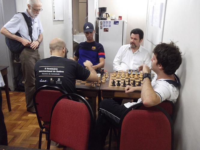 Antes do torneio começar, Sérgio Sundaus (em pé), Pádua e Léo observam uma partida Blitz entre André Kemper e Renato Werner (de costas)