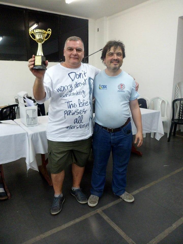 Márcio de Lucca Cardoso ergue seu troféu ao lado de Marcelo Einhorn