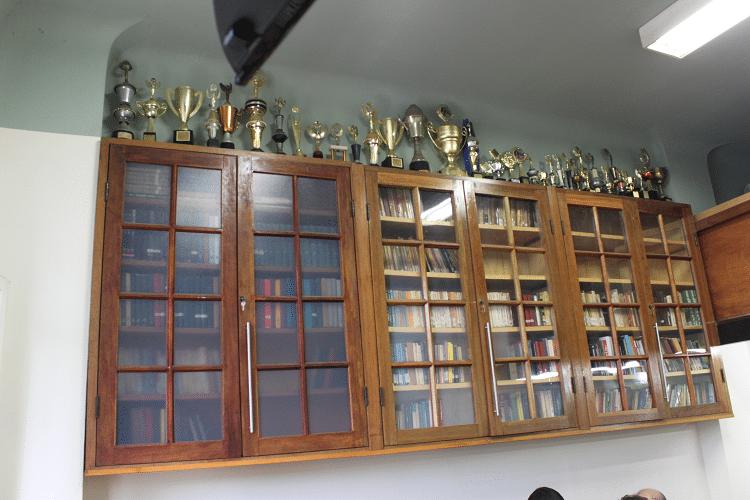 A estante da Biblioteca Dijalma Caiafa e a coleção de Troféus conquistados pelo clube