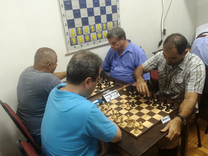3 - Na mesa 3, Fernando Madeu, de brancas, enfrenta Carlos Eduardo Nunes Na mesa 4, Claide Teixeira Barros enfrenta Sérgio Murilo