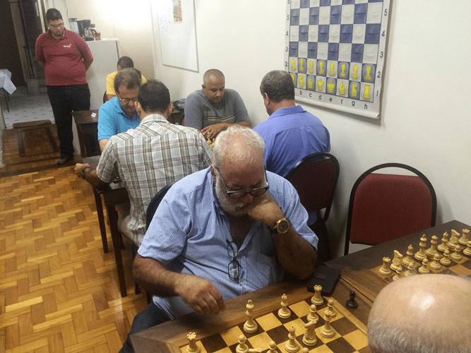 6 - Em primeiro plano, jogando de brancas, Henrique Mangine. No fundo da sala, em pé, Rodrigo Alves Vieira