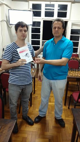 Leo Ramos Simões recebendo das mãos de Fernando Madeu o livro prêmio que ganhou pela conquista do Rápido FIDE de Agosto. Tal livro foi uma doação do poeta Ricardo França, recém associado à ALEX.